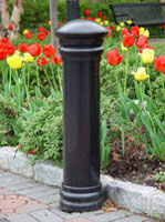 Garden City bollard protecting a flowerbed.